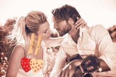 Zusammengesetztes Bild des gutaussehenden Mannes seine Freundin mit Gitarre ein Ständchen bringend Lizenzfreies Stockbild