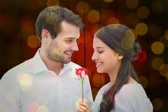 Zusammengesetztes Bild des gutaussehenden Mannes seiner Freundin eine Rose anbietend Lizenzfreies Stockfoto