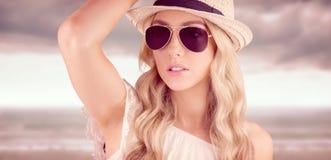 Zusammengesetztes Bild des herrlichen blonden Hippies, der mit Strohhut aufwirft Stockfotos
