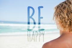 Zusammengesetztes Bild des jungen blonden Mannes, der das Meer beim Ein Sonnenbad nehmen betrachtet Lizenzfreie Stockfotografie