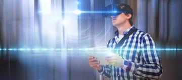 Zusammengesetztes Bild des jungen Mannes digitale Tablette bei der Anwendung von Simulatorgläsern der virtuellen Realität halten Lizenzfreie Stockbilder
