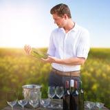 Zusammengesetztes Bild des jungen Mannes Weinflasche durch Gläser auf Fass halten lizenzfreie stockbilder