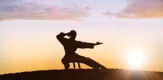 Zusammengesetztes Bild des Kämpfers Karateposition durchführend lizenzfreies stockfoto