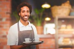 Zusammengesetztes Bild des Kellners Tasse Kaffee auf einem Behälter halten Stockfotos