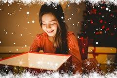 Zusammengesetztes Bild des kleinen Mädchens ein glühendes Weihnachtsgeschenk öffnend Stockfotografie