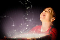 Zusammengesetztes Bild des kleinen Mädchens ein magisches Weihnachtsgeschenk öffnend Stockfotos