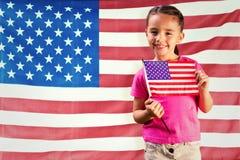 Zusammengesetztes Bild des kleinen Mädchens mit amerikanischer Flagge lizenzfreies stockbild