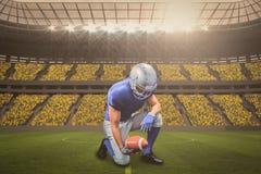 Zusammengesetztes Bild des knienden Spielers des amerikanischen Fußballs beim Halten des Balls mit 3d Stockbilder