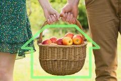 Zusammengesetztes Bild des Korbes der Äpfel, die durch ein junges Paar getragen werden Stockbilder