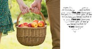 Zusammengesetztes Bild des Korbes der Äpfel, die durch ein junges Paar getragen werden Stockfoto