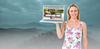 Zusammengesetztes Bild des lächelnden blonden haltenen Laptops und der Aufstellung Lizenzfreies Stockbild