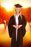 Zusammengesetztes Bild des lächelnden blonden Studenten in der graduierten Robe Stockfotos