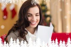 Zusammengesetztes Bild des lächelnden Brunette auf dem Couchlesebuchstaben am Weihnachten Stockbild