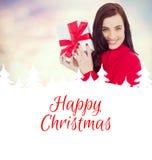 Zusammengesetztes Bild des lächelnden Brunette im roten Pulloverhut, der ein Geschenk zeigt vektor abbildung
