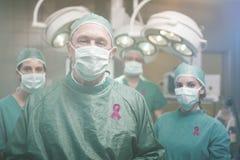 Zusammengesetztes Bild des lächelnden Chirurgen aufwerfend mit einem Team lizenzfreies stockbild