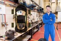 Zusammengesetztes Bild des lächelnden Mechanikers mit den Armen kreuzte bereitstehenden Reifen Lizenzfreie Stockfotos