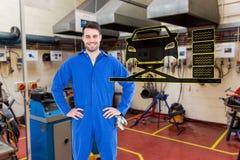 Zusammengesetztes Bild des lächelnden Mechanikers mit den Händen auf den Hüften, die Reifen bereitstehen Stockfotografie