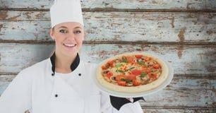 Zusammengesetztes Bild des lächelnden weiblichen Chefs mit Pizza Stockbild