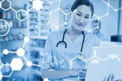 Zusammengesetztes Bild des lächelnden weiblichen Chirurgen, der einen Laptop verwendet Lizenzfreie Stockfotos