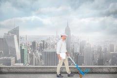 Zusammengesetztes Bild des Lieferers leere Laufkatze auf weißem Hintergrund drückend Lizenzfreies Stockbild
