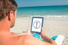 Zusammengesetztes Bild des Mannes, der digitale Tablette auf Klappstuhl am Strand verwendet Lizenzfreies Stockfoto
