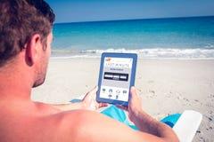 Zusammengesetztes Bild des Mannes, der digitale Tablette auf Klappstuhl am Strand verwendet Stockfoto