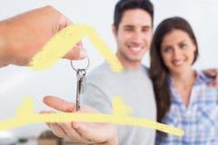 Zusammengesetztes Bild des Mannes, der einen Hausschlüssel gegeben wird Lizenzfreie Stockfotos