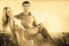 Zusammengesetztes Bild des Mannes seine hübsche Freundin tragend, die an der Kamera lächelt Lizenzfreies Stockfoto