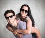 Zusammengesetztes Bild des Mannes seiner hübschen Freundin ein Doppelpol gebend Stockbilder