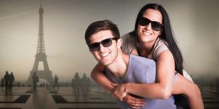 Zusammengesetztes Bild des Mannes seiner hübschen Freundin ein Doppelpol gebend Lizenzfreies Stockfoto