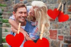 Zusammengesetztes Bild des Mannes seiner hübschen Freundin ein Doppelpol gebend Lizenzfreie Stockfotografie