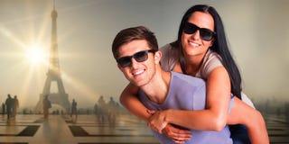 Zusammengesetztes Bild des Mannes seiner hübschen Freundin ein Doppelpol gebend Lizenzfreie Stockfotos