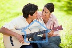 Zusammengesetztes Bild des Mannes und sein Freund betrachten einander, während er die Gitarre spielt Lizenzfreie Stockfotografie