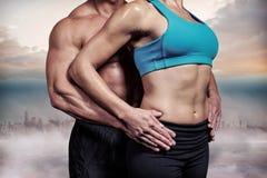Zusammengesetztes Bild des Mittelteils der gesunden Paare mit den Händen auf Hüfte lizenzfreies stockfoto