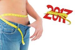 Zusammengesetztes Bild des mittleren Abschnitts der messenden Taille der Frau in große sortierte Jeans Lizenzfreies Stockbild