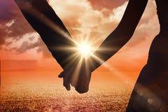 Zusammengesetztes Bild des mittleren Abschnitts des Jungvermähltenpaarhändchenhaltens im Park Lizenzfreies Stockfoto