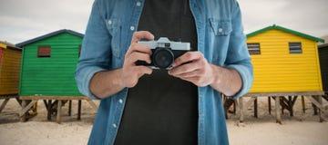 Zusammengesetztes Bild des mittleren Abschnitts des Mannes Kamera halten Stockfotografie