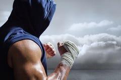 Zusammengesetztes Bild des muskulösen Mannes in der blauen Haube mit kämpfender Position Lizenzfreies Stockfoto