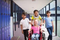 Zusammengesetztes Bild des netten behinderten Schülers, der an der Kamera mit ihren Freunden lächelt Stockfoto