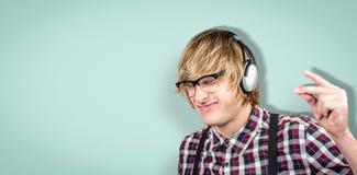 Zusammengesetztes Bild des netten blonden Hippies, der Musik hört Lizenzfreie Stockfotos
