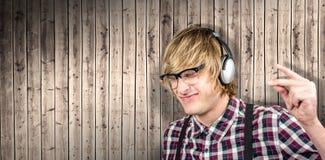 Zusammengesetztes Bild des netten blonden Hippies, der Musik hört Stockfotografie