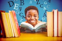 Zusammengesetztes Bild des netten Jungenlesebuches in der Bibliothek Stockfotos