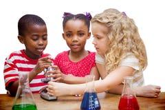 Zusammengesetztes Bild des netten Schülers schauend durch Mikroskop Stockfotografie