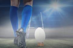Zusammengesetztes Bild des niedrigen Abschnitts des Rugbyspielers ungefähr, zum des Balls zu treten Stockfoto