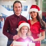 Zusammengesetztes Bild des Porträts der Familie in der Weihnachtskleidung, die mit Geschenken steht Lizenzfreie Stockbilder