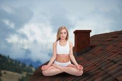 Zusammengesetztes Bild des Porträts der jungen Frau sitzend in Lotussitz mit Augen clos Lizenzfreie Stockfotografie