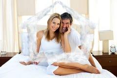 Zusammengesetztes Bild des Porträts der Liebhaber, die auf Bett sitzen Stockbilder