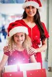 Zusammengesetztes Bild des Porträts der Mutter und Tochter im Weihnachten bekleiden Stellung mit Geschenken Stockfotos