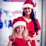 Zusammengesetztes Bild des Porträts der Mutter und Tochter im Weihnachten bekleiden Stellung mit Geschenken Stockfotografie