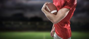Zusammengesetztes Bild des Porträts des überzeugten Spielers des amerikanischen Fußballs im roten Trikot, das Ball hält Stockfoto